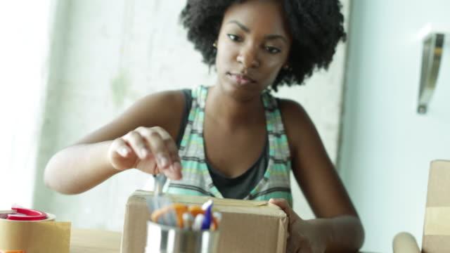 vidéos et rushes de cu young woman selects pen and writes address on package. - paquet