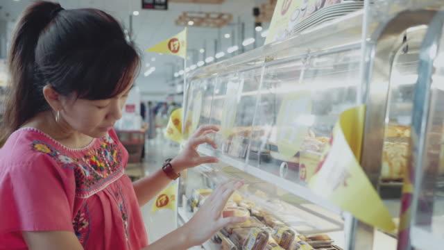 若い女性は店の棚のパンを選ぶ - 一斤点の映像素材/bロール