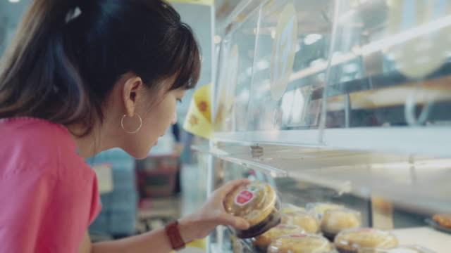 young woman selects the bread on the shelves in the store - cream cake stock videos & royalty-free footage