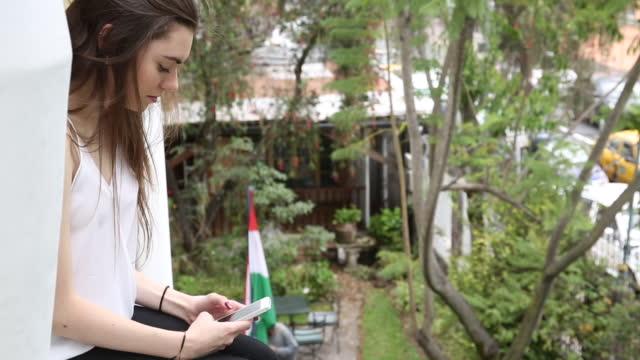 vídeos de stock e filmes b-roll de young woman sends text on villa windowsill - cabelo natural