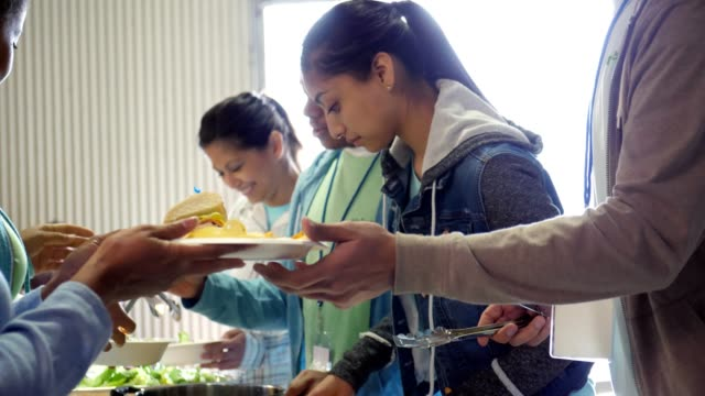 young woman serves community in soup kitchen - community stock videos & royalty-free footage
