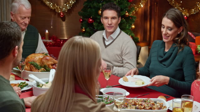 Young woman serving mashed potatoes to other family members at Christmas dinner