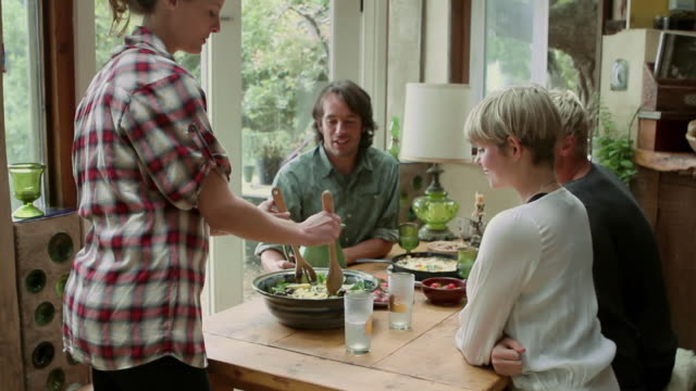 ms slo mo young woman serving salad among friends and lovers / big sur, california, usa - dining table stock videos & royalty-free footage