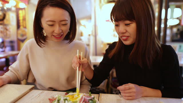 young woman serving salad into small dishes in izakaya bar - catering building stock videos & royalty-free footage