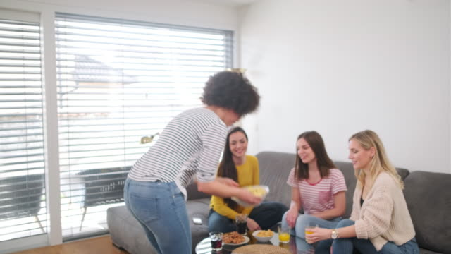 young woman serving snacks to friends at home - coffee table stock videos & royalty-free footage