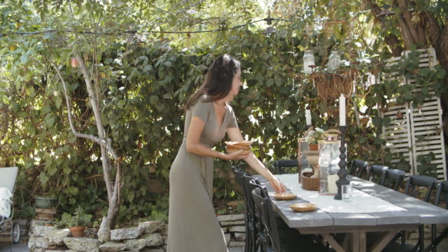 young woman setting the table outdoors - lunch stock videos & royalty-free footage