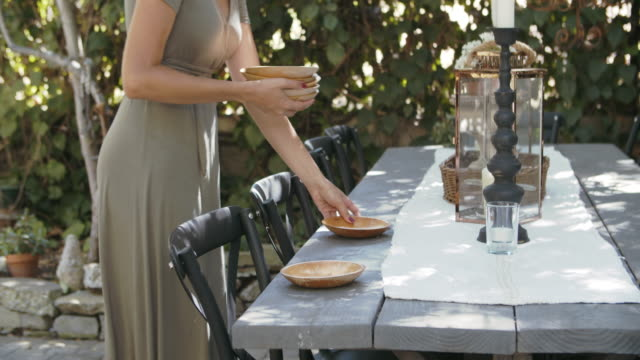 cu young woman setting the table outdoors - setting the table stock videos & royalty-free footage