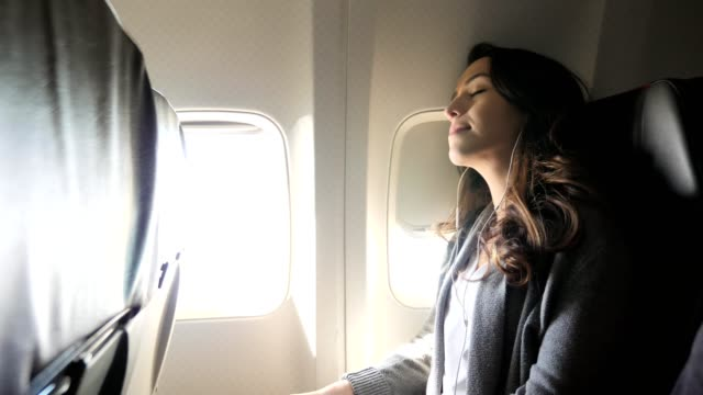 young woman settles in for a nap during a long flight - in ear headphones stock videos & royalty-free footage