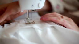 Young woman sewing on the sewing machine.