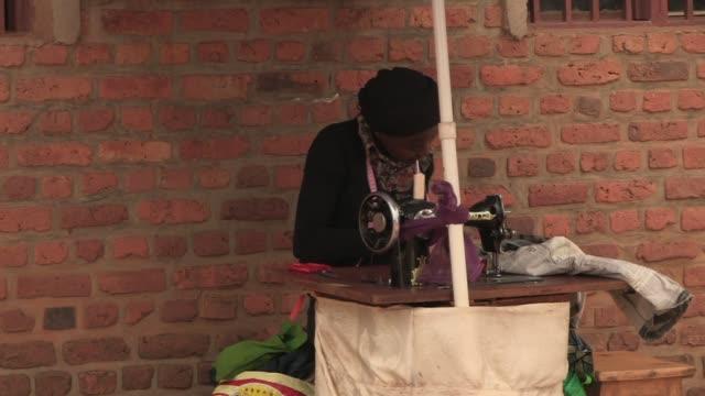 stockvideo's en b-roll-footage met young woman sews garments outdoors in rural rwanda - kleding