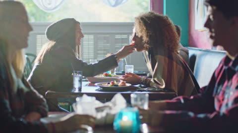 vídeos y material grabado en eventos de stock de young woman shares delicious bite with her partner on lunch date in local cafe. - plato de comida