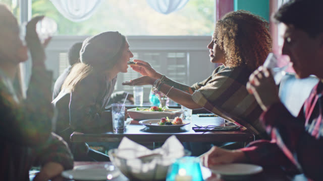 vídeos de stock e filmes b-roll de young woman shares delicious bite with her partner on lunch date in local cafe. - carinhoso