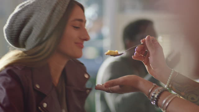 vídeos de stock e filmes b-roll de young woman shares delicious dessert with partner on lunch date in local cafe. - cheio