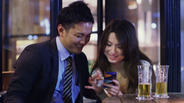 MS Young woman shares something on mobile phone with man in a bar / Tokyo, Japan