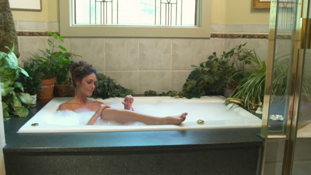 WS DS Young woman shaving her legs in bathtub / Salt Lake City, Utah, USA