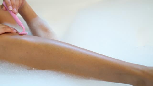 CU PAN Young woman shaving her legs in bathtub / Salt Lake City, Utah, USA