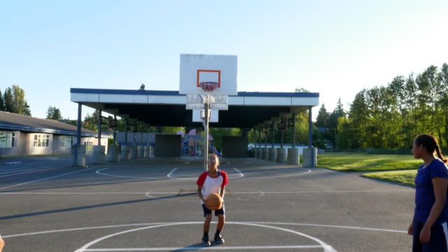 MS TU Young woman shooting free throw while playing basketball with sisters on outdoor court on summer evening