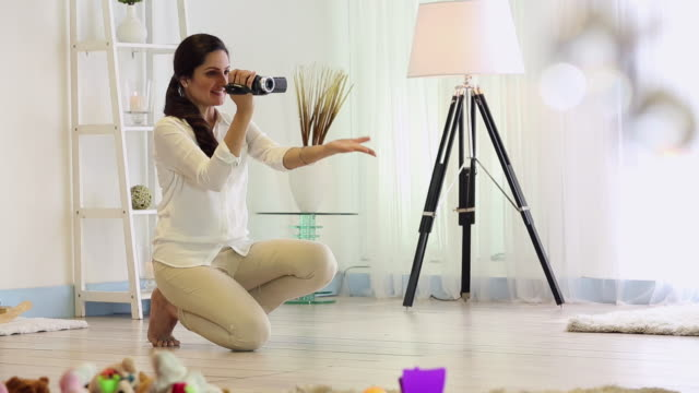 Young woman shooting video of her son with a camera