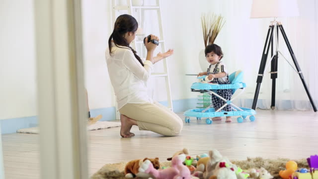 young woman shooting video of her son with a camera - 撮影点の映像素材/bロール