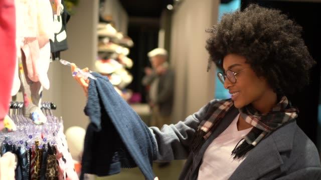 giovane donna che fa shopping per i vestiti per bambini - abbigliamento da neonato video stock e b–roll