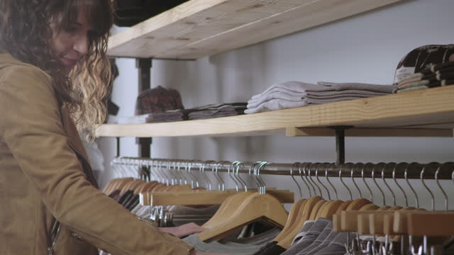 young woman shopping for clothes sorts through hangars on rack in downtown store. - clothing store stock videos and b-roll footage
