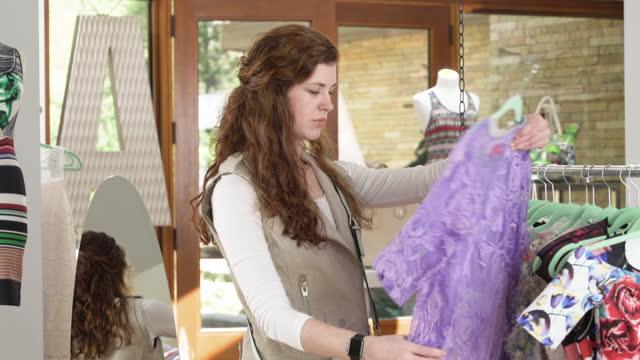 vídeos de stock e filmes b-roll de young woman shopping for clothes - saldos
