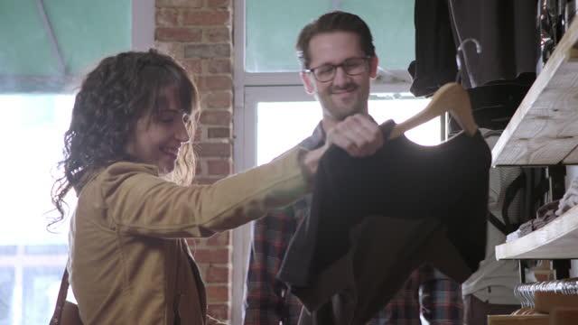 若い女性はボーイフレンドと一緒に服を買い物をしてシャツを選ぶが、彼は首を横に振って笑う。 - ハンガー点の映像素材/bロール
