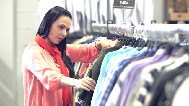 Young woman shopping for men's shirts in clothing store