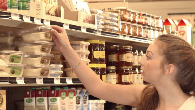cu young woman shopping for middle eastern food items in ethnic food store - supermarkt einkäufe stock-videos und b-roll-filmmaterial