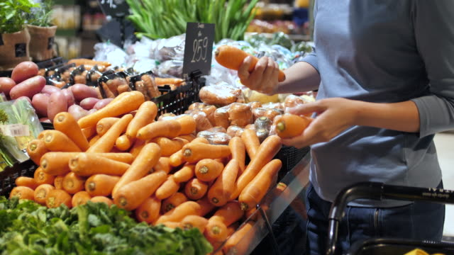 vidéos et rushes de la jeune femme faisant des emplettes le légume frais choisissent un fruit sur le marché. sain - produit bio