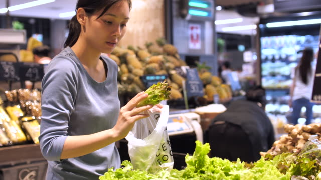 young woman shopping fresh vegetable in super market - retail stock videos & royalty-free footage