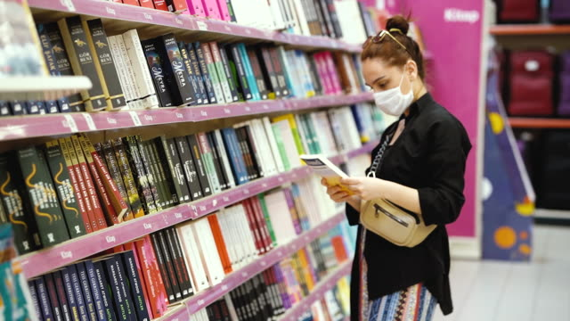 young woman shopping in a book section in the store and wearing protective medical mask - bookstore stock videos & royalty-free footage