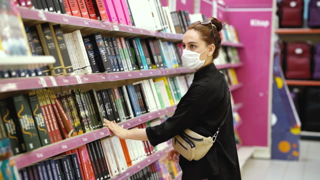 young woman shopping in a book section in the store and wearing protective medical mask - part of a series stock videos & royalty-free footage