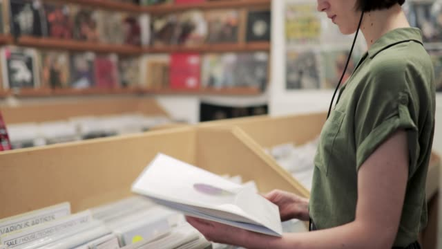 vídeos y material grabado en eventos de stock de joven mujer de compras en una tienda de registro - tienda de discos