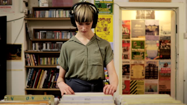 young woman shopping in a record store - ascoltare video stock e b–roll
