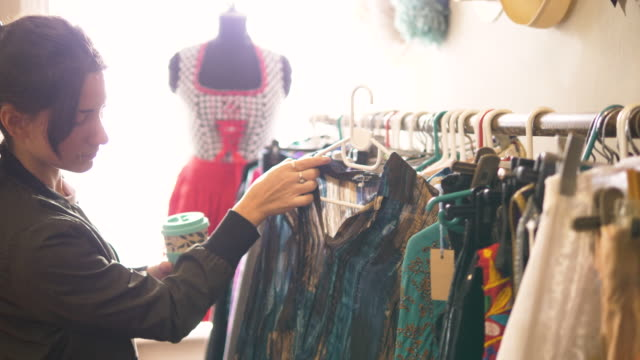young woman shopping in a vintage clothes shop - second hand stock videos & royalty-free footage