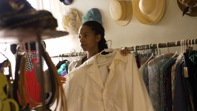 young woman shopping in a vintage clothes shop - afro caribbean ethnicity stock videos and b-roll footage