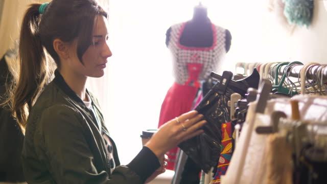 vídeos de stock, filmes e b-roll de young woman shopping in a vintage clothes shop - fora de moda estilo