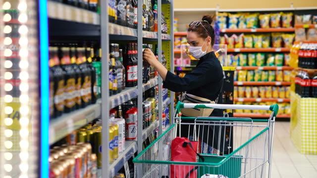 食料品店のアルコールセクションで買い物をし、保護医療マスクを着用する若い女性 - メガストア点の映像素材/bロール