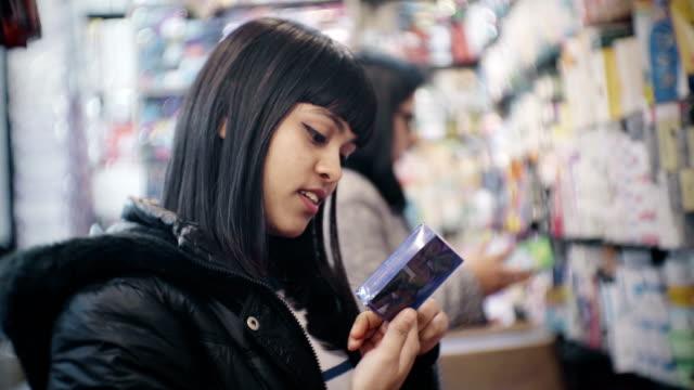 vídeos de stock, filmes e b-roll de jovem mulher às compras em geral de loja. - mercado noturno
