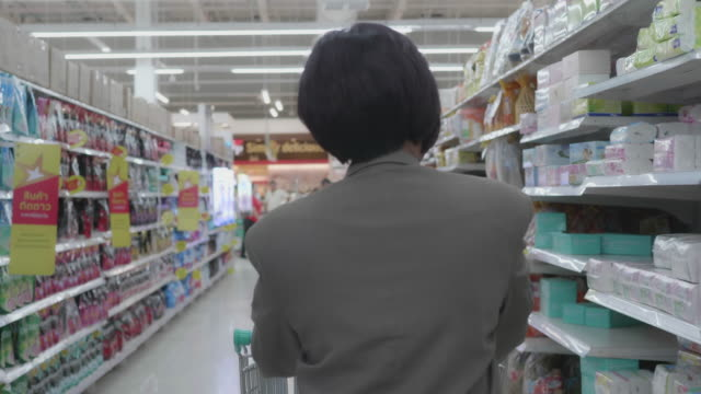 young woman shopping in supermarket. - shelf stock videos & royalty-free footage