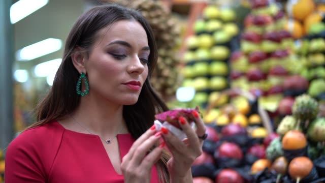 vídeos y material grabado en eventos de stock de joven mujer de compras en el mercado local - encontrar