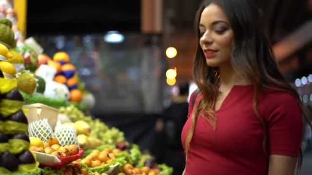 vídeos y material grabado en eventos de stock de joven mujer de compras en el mercado local - américa del sur
