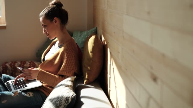 vídeos de stock e filmes b-roll de young woman shopping online at comfortable sunny home - confortável