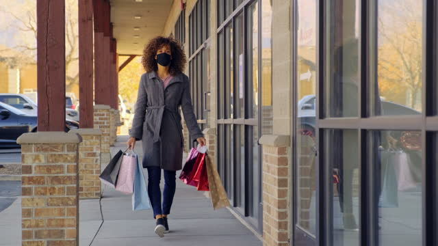 young woman shopping with face mask on for protection - walkable city stock videos & royalty-free footage
