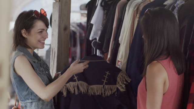 young woman shopping with friend holds up western shirt with tassels and laughs - mercato delle pulci video stock e b–roll