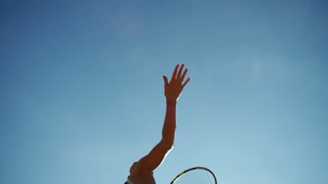 vídeos de stock e filmes b-roll de young woman shot from below in slow motion making overhand tennis serve - raqueta