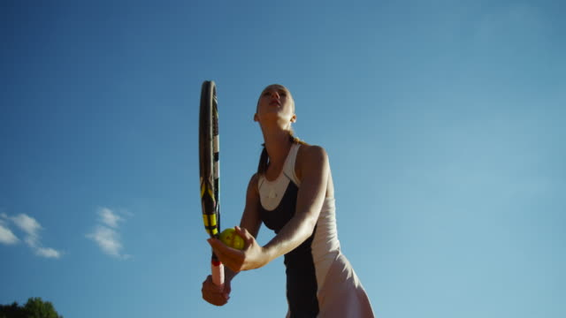 young woman shot from below in slow motion making overhand tennis serve - テニス点の映像素材/bロール