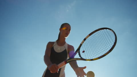 vidéos et rushes de young woman shot from below in slow motion making overhand tennis serve - ball