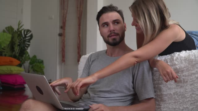 young woman showing her husband something on lap - husband stock videos & royalty-free footage